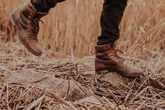 Foto van oude mannetjesschoenen Mens in bruine broeken en laarzen die in motie op stenen met stoppelveld zijn Modderig schoeisel  royalty-vrije stock afbeelding
