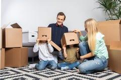 Foto van ouders en kinderen die met kartondozen op hun hoofden in nieuwe flat zitten royalty-vrije stock foto