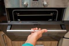 Foto van oven en menselijke hand royalty-vrije stock foto
