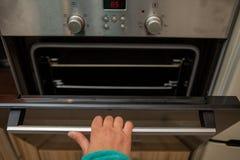 Foto van oven en menselijke hand stock afbeeldingen