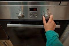 Foto van oven en vrouwenhand stock foto