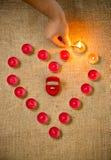 Foto van persoonsverlichting op kaarsen in vorm van hart Royalty-vrije Stock Afbeeldingen
