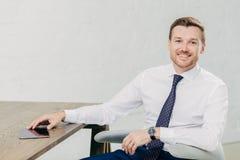 Foto van positieve jonge succesvolle mannelijke ondernemer de gekleed in elegant wit overhemd met band, bekijkt positief camera,  stock foto