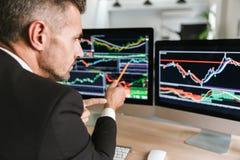 Foto van slimme zakenmanzitting bij lijst in bureau en het werken met grafiek en grafieken aan computer royalty-vrije stock foto's