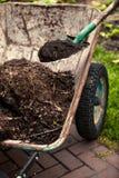 Foto van spade die grond in oude kruiwagen zetten Stock Afbeeldingen