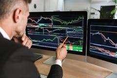 Foto van succesvolle zakenmanzitting bij lijst in bureau en het werken met grafiek en grafieken aan computer stock fotografie