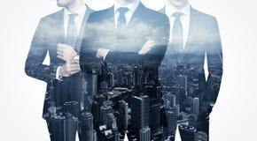 Foto van trio modieuze volwassen zakenman die in kostuum dragen Dubbele blootstelling, panorama eigentijdse stad royalty-vrije stock afbeelding