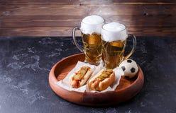 Foto van twee glazen bier en hotdogs op houten dienblad met voetbal Royalty-vrije Stock Afbeelding
