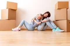 Foto van twee meisjes die op vloer onder kartondozen zitten stock afbeelding