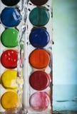 Foto van van de waterplons en kleur verven op blauwe achtergrond Royalty-vrije Stock Afbeelding