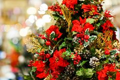 Foto van verfraaide Kerstmissparren met rode bloemen, denneappels, bessen in opslag royalty-vrije stock afbeeldingen