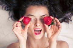 Foto van verleidelijke vrouwelijke holdingsaardbei dichtbij gezicht eyeys, het roodharige sensuele vrouw van het close-upportret  Stock Foto