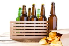 Foto van verschillende volledige bierflessen zonder etiketten en document pak chips op lijst royalty-vrije stock afbeelding