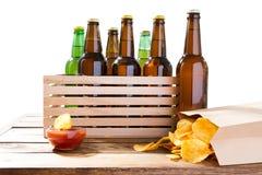 Foto van verschillende volledige bierflessen zonder etiketten en document pak chips op lijst, souces stock afbeeldingen