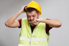 Foto van verstoorde bouwer in gele helm in vest op lege grijze achtergrond stock afbeelding