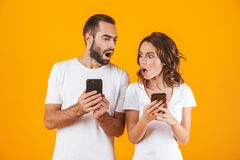 Foto van verwarde die man en vrouwenholding en het gluren bij celtelefoons, over gele achtergrond wordt geïsoleerd stock foto