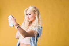 Foto van vrolijke mooie jonge vrouw die mobiele die telefoon houden over gele achtergrond wordt ge?soleerd royalty-vrije stock afbeelding
