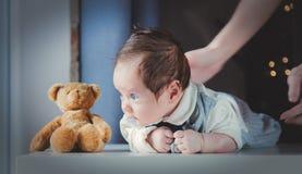 Foto van weinig zuigeling in moeder` s handen met teddybeerstuk speelgoed royalty-vrije stock afbeelding