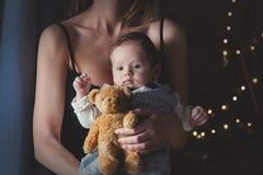 Foto van weinig zuigeling in moeder` s handen met teddybeerstuk speelgoed royalty-vrije stock afbeeldingen