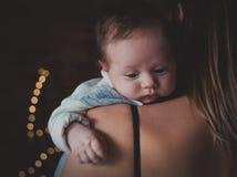 Foto van weinig zuigeling op moeder` s schouder royalty-vrije stock afbeeldingen