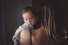 Foto van weinig zuigeling op moeder` s schouder stock fotografie
