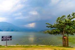 Foto van wolk, meer, berg, boom en bezinning in water dichtbij Pokhara-Meer in Katmandu Nepal Breuk in portret, landschap stock fotografie