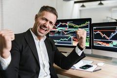Foto van zich het extatische zakenman verheugen terwijl het werken in bureau met digitale grafiek en grafieken royalty-vrije stock afbeelding