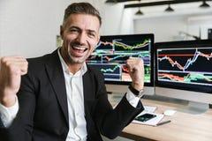 Foto van zich het gelukkige zakenman verheugen terwijl het werken in bureau met digitale grafiek en grafieken stock fotografie