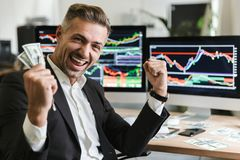 Foto van zich het Kaukasische zakenman verheugen terwijl het werken in bureau met digitale grafiek en grafieken royalty-vrije stock foto