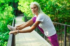 Foto van zich sportenvrouw het uitrekken op houten brug Stock Afbeeldingen