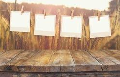 A foto velha do polaroid molda a suspensão em uma corda com a tabela da placa de madeira do vintage na frente da paisagem do camp Imagens de Stock
