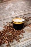 Foto vertical de um copo do café preto perfumado em um fundo de feijões de café e de uma tabela de madeira foto de stock royalty free