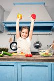 Foto vertical de uma menina bonita com suas mãos levantadas, em suas mãos guarda uma pimenta búlgara imagem de stock royalty free