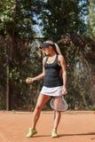 Foto vertical del jugador de tenis rubio de la señora con la bola a disposición en la corte al aire libre Imagenes de archivo