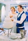 Foto vertical dos recém-casados felizes que cortam a primeira parte do bolo de casamento fotografia de stock royalty free