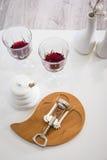 Foto vertical A vista da parte superior Vinho tinto, vidro de vinho, corkscrew tabela branca, canto da decoração Em casa Restaura Imagem de Stock Royalty Free
