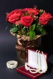 Foto verticale del mazzo dei fiori vicino alla scatola con le perle su buio fotografie stock