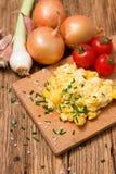 Foto verticale delle uova rimescolate sul tagliere Immagine Stock