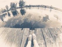 Foto vieja de la vendimia Una muchacha en zapatos azules se sienta en el embarcadero de madera cerca del río del lago fotos de archivo libres de regalías