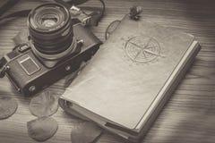foto vieja de una cámara con un diario del viaje y los pétalos de la flor en la decoración Foto de archivo