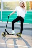 Foto in voller Länge der gelockten athletischen Frau, die auf Roller im Park tritt stockfotos