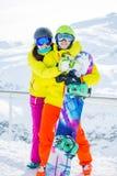 Foto in voller Länge der sportlichen Frau und des Mannes mit Snowboard gegen Hintergrund von Bergen Lizenzfreies Stockbild