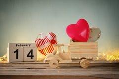 Foto vom 14. Februar des hölzernen Weinlesekalenders mit hölzernem Spielzeuglastwagen mit Herzen vor Tafel Stockbild