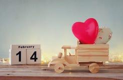 Foto vom 14. Februar des hölzernen Weinlesekalenders mit hölzernem Spielzeuglastwagen mit Herzen vor Tafel Stockfotos