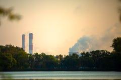 Foto von Bäumen, Fluss, industrielle Rohre mit Rauche stockfoto