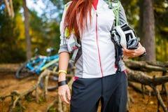 Foto von Brunette mit dem Sturzhelm, der gegen Hintergrund des Fahrrades steht Stockfotos