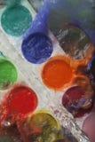 Foto von den eingestellten Farbfarben spritzte mit Wasser Stockbilder