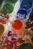 Foto von den Farben, die mit Wasser gespritzt werden Stockfotos