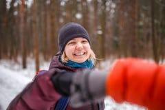 Foto von den Leuten, die Händedruck im Winterwald machen Stockbild