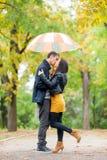 Foto von den netten Paaren, die unter Regenschirm auf dem w umarmen und küssen Stockfotografie